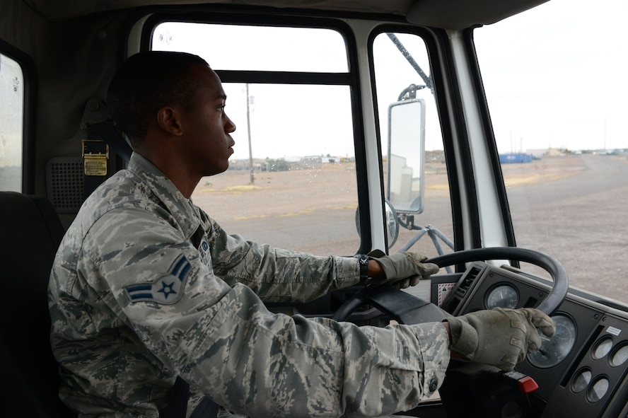 Airman 1st Class Demetrius Smith, 56th Civil Engineer Squadron heavy equipment operator, drives a street sweeper along perimeter road at Luke Air Force Base, Ariz., Jan. 5, 2015. Street sweeping, heavy equipment movement and excavators for trenches are utilized to assist various jobs around the base and 56th CES. (U.S. Air Force photo by Senior Airman James Hensley)