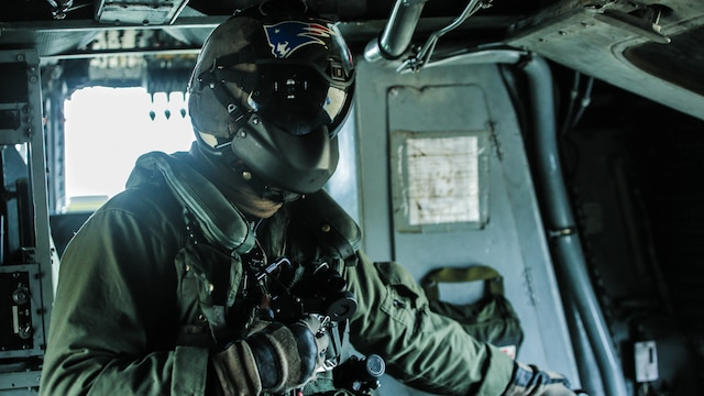 Lance Cpl. Jacob Burnette, a crew chief with Marine Heavy Helicopter Squadron 302, looks out the window as he prepares to conduct external lifts in conjunction with Combat Logistics Battalion 2 at Marine Corps Base Camp Lejeune, N.C., Jan. 6, 2016. The crew chief's responsibilities when conducting external lifts are to direct the pilot and co-pilot as they attach the load onto the CH-53E Super Stallion allowing the pilot to solely focus on maneuvering the aircraft.