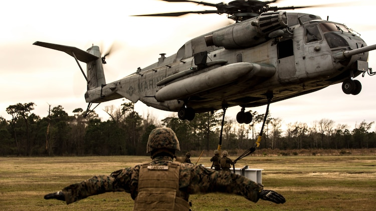 U.S. Marines with Combat Logistics Battalion 2 conduct external lifts in conjunction with Marine Heavy Helicopter Squadron 302 at Marine Corps Base Camp Lejeune, N.C., Jan. 6, 2016. The Marines with CLB 2 are responsible for directing the aircraft from the ground and attaching the load with the help from the crew chief, thus giving them the capability to move heavy loads in a combat environment.