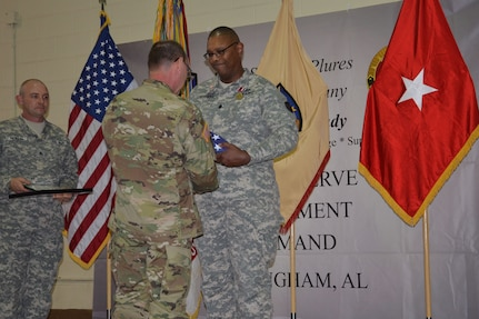 Brig. Gen. Jeffrey Doll presents Lt. Col. Alan Sconiers with a retirement flag during his retirement ceremony. Sconiers' career spanned over 29 years of military service in the Army National Guard and Army Reserve.  He received the Meritorious Service Medal along with several certificates of appreciation and a memento of an eagle made out of Alabama clay from the Army Reserve Sustainment Command (also pictured is Staff Sgt. William Hollis, awards bearer).