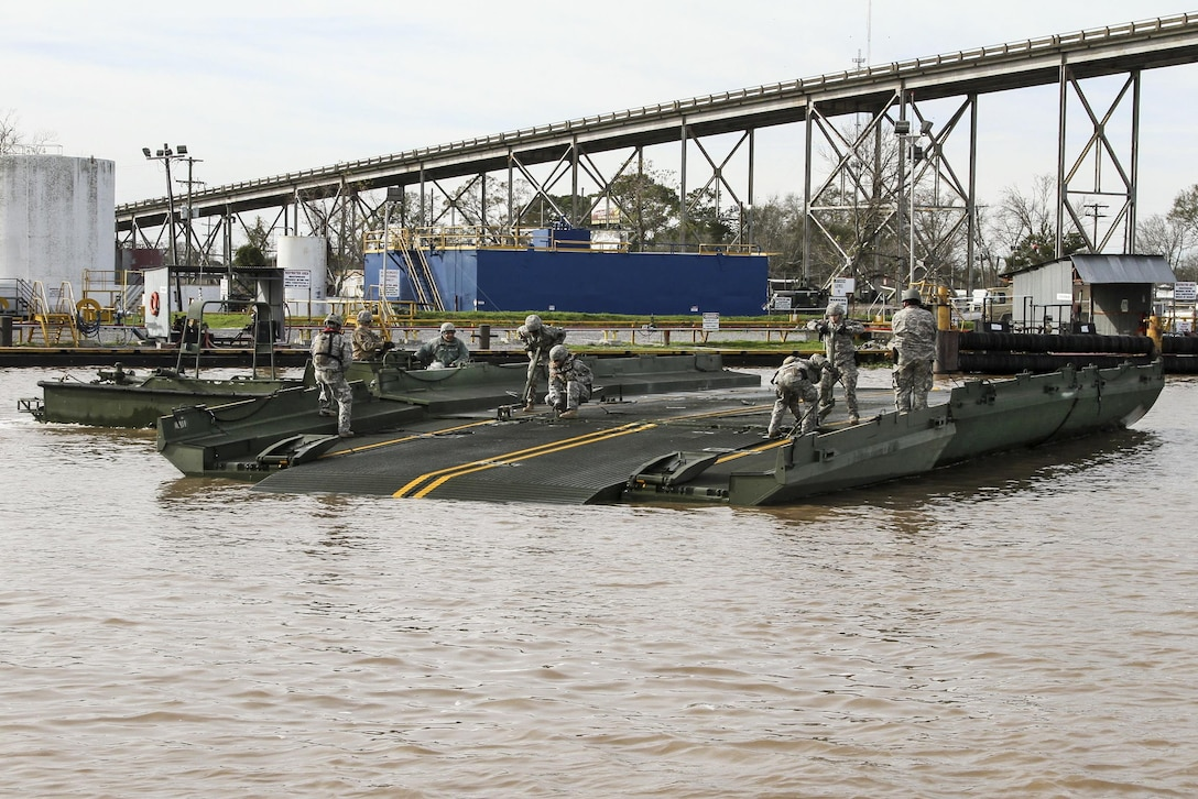 Soldiers assemble a ribbon bridge in Amelia, La., Jan. 8, 2016, to transport crew, equipment and supplies to build a 12,550-foot levee on Avoca Island before expected river flooding in Morgan City, La. Louisiana Army National Guard photo by Spc. Garrett Dipuma