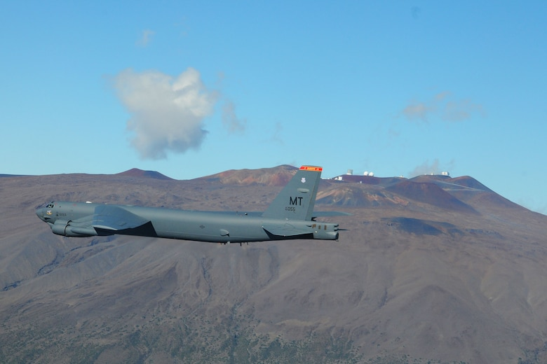 With the Mauna Kea volcano in the background, a B-52 Stratofortress from the 23rd Expeditionary Bomb Squadron, flies over the Mauna Loa volcano, Hawaii, on Dec. 28, 2015, during a training mission. Two B-52 aircrews currently assigned here as part of the U.S. Pacific Command's continuous bomber presence, conducted a bomber Airmen heritage flyby of the Mauna Loa volcano. The flyby was part of the 80th anniversary of the 23rd Bombardment Squadron using bombs to divert lava flow from the volcano that threatened the town of Hilo, Hawaii, in 1935. (Courtesy photo)