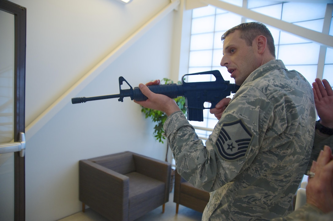 Master Sgt. Cam Vaillant, 446th Aeromedical Evacuation Squadron, practices tactical formation as he enters a room carrying a mock rifle Jan. 10, 2016, at Hangar 12. This training is part of the hands-on portion of an expeditionary active shooter response course. (U.S. Air Force Reserve photo by Staff Sgt. Madelyn McCullough)