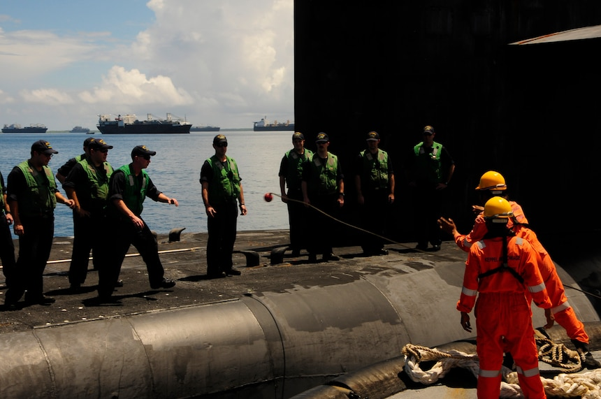 160107-N-PN275-032 DIEGO GARCIA, British Indian Ocean Territory (Jan. 7, 2016) Sailors from guided-missile submarine USS Florida (SSGN 728) receive a mooring line from a tug boat to be brought alongside submarine tender USS Emory S. Land (AS 39) in Diego Garcia. Emory S. Land is a forward deployed expeditionary submarine tender on an extended deployment conducting coordinated tended moorings and afloat maintenance in the U.S. 5th and 7th Fleet areas of operations. (U.S. Navy photo by Mass Communication Specialist 3rd Class Zachary A. Kreitzer/Released)