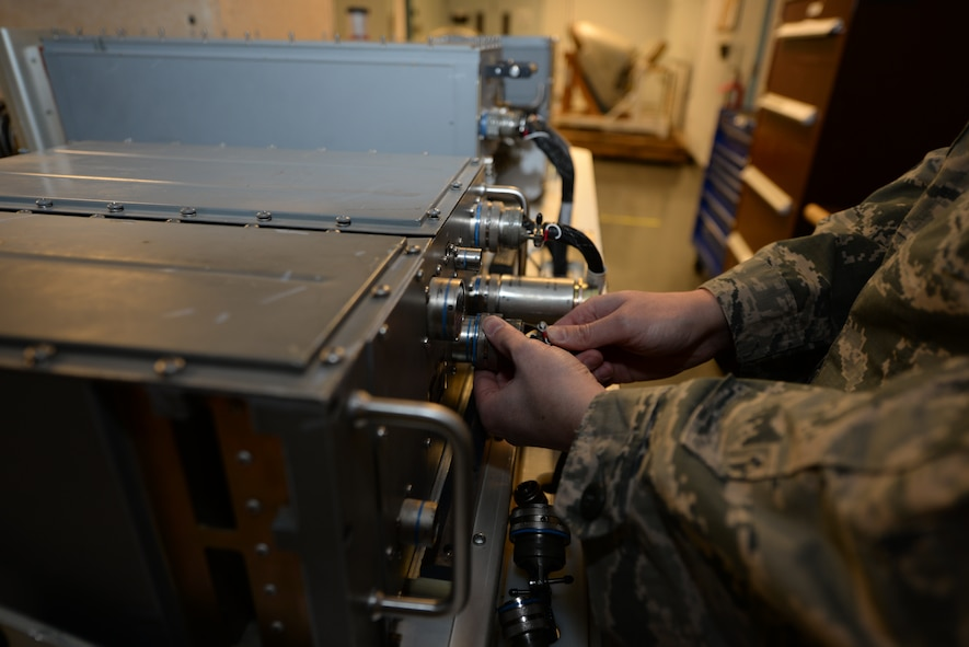 Staff Sgt. Lary Eyre, 28th Maintenance Squadron avionics team leader, connects an electrical plug to a radar video signal processor unit at Ellsworth Air Force Base, S.D., Jan. 6, 2016. The RSVP generates signals that transmit to a radar target indicator, which displays what the aircraft can sense on the ground onto a screen. (U.S. Air Force photo by Airman Sadie Colbert/Released)