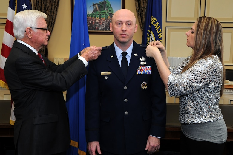 "Lt. Col. Danny Davis, Air Force District of Washington A1 deputy director, pins on the rank of Colonel with the assistance of his wife Daniella and U.S Congressman Hal Rogers, Kentucky's 5th Congressional District, during his promotion ceremony at the U.S. Capitol Building, Washington D.C., January 7, 2016. ""He's served his nation as a member of the U.S. Air Force for over 20 years and has represented America to allies around the world,"" said Rogers. ""As a native Kentuckian, he has also sought out opportunities to give back to his home state at every stage of his career."" (U.S. Air Force photo/Tech. Sgt. Matt Davis)"