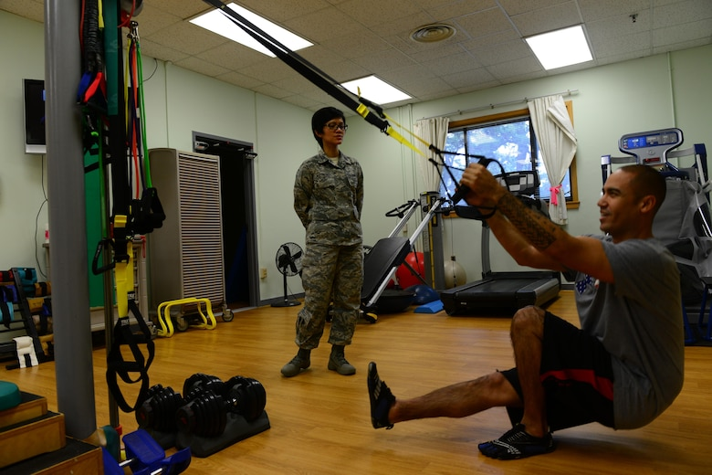 U.S. Air Force Capt.  Jacqueline Astrero, 8th Medical Operations Squadron health promotion flight commander and physical therapist, coaches Tech. Sgt. Anthony Flores, 8th MDOS physical therapy technician during therapy session at Kunsan Air Base, Republic of Korea, Jan. 7, 2016. A physical therapy technician's job is to assist the commander and return active duty members to full duty status, making them fit to fight. (U.S. Air Force photo by Senior Airman Ashley L. Gardner/Released)
