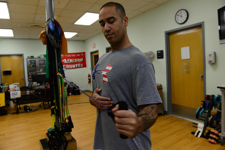 U.S. Air Force Tech. Sgt. Anthony Flores, 8th Medical Operations Squadron physical therapy technician, demonstrates arm exercises during a therapy session at Kunsan Air Base, Republic of Korea, Jan. 7, 2016. A physical therapy technician's job is to assist the commander and return active duty members to full duty status, making them fit to fight. (U.S. Air Force photo by Senior Airman Ashley L. Gardner/Released)