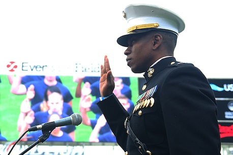 Capt. Ronnie Jones swears young men and women into the Marine Corps during the TaxSlayer Bowl halftime show Jan. 2, 2016, at EverBank Field in Jacksonville, Fla. The oath was taken under the watchful gaze of more than 25,000 people in the stadium. Jones is the Executive Officer of Recruiting Station Jacksonville in Jacksonville, Fla. (Official Marine Corps photo by Cpl. John-Paul Imbody/Released)