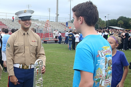 Cpl. Sterling Davis talks with high school band students about the opportunities the Marine Corps offers them in the music field Jan. 1, 2016, at Terry Park High School in Jacksonville, Fla. Clark is a part of the Parris Island Marine Band who will be playing at the TaxSlayer Bowl halftime show with high school bands from across the country Jan. 2, 2016. Davis plays the horn in the Parris Island Marine Band. (Official Marine Corps photo by Cpl. John-Paul Imbody/Released)
