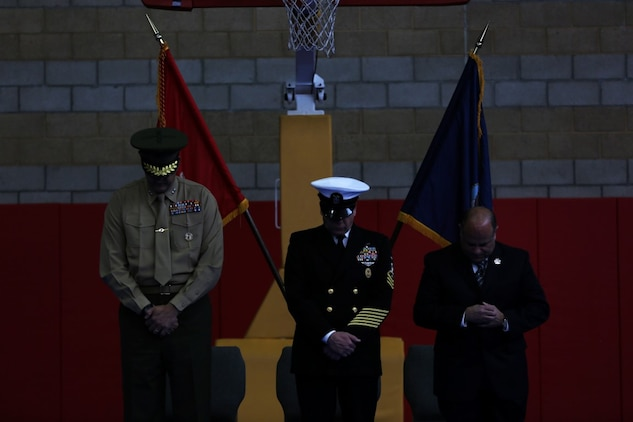 Master Chief Petty Officer Robert Lemons (center), the command master chief of the 1st Marine Division, bows his head along with Maj. Gen. Daniel O'Donohue (left), command general of the 1st Mar. Div., during Lemons' retirement ceremony aboard Marine Corps Base Camp Pendleton, California, Jan. 8, 2016. Lemons enlisted in the U.S. Navy in 1986 and served a majority of his time in the service as a corpsman.