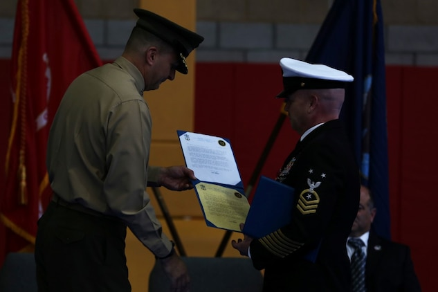 Master Chief Petty Officer Robert Lemons (right), the command master chief with of the 1st Marine Division, receives his retirement certificates from Maj. Gen. Daniel O'Donohue (left), commanding general of the 1st Mar. Div., during Lemons' retirement ceremony aboard Marine Corps Base Camp Pendleton, Calif., Jan. 8, 2016. Lemons enlisted in the U.S. Navy in 1986 and served a majority of his time in the service as a corpsman.