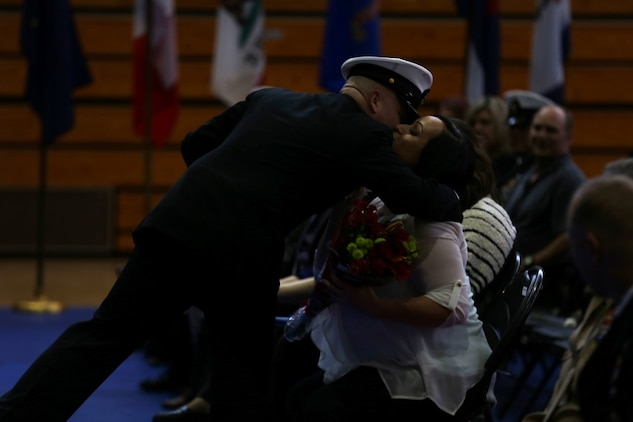 Master Chief Petty Officer Robert Lemons (center), the command master chief of the 1st Marine Division, presents his wife with a bouquet of flowers during his retirement ceremony aboard Marine Corps Base Camp Pendleton, Calif., Jan. 8, 2016. Lemons enlisted in the U.S. Navy in 1986 and served a majority of his time in the service as a corpsman.