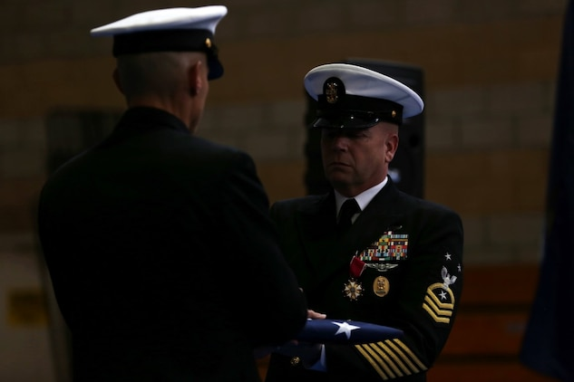 Master Chief Petty Officer Robert Lemons (right), the command master chief of the 1st Marine Division, receives a folded flag during the Old Glory presentation as part of his retirement ceremony aboard Marine Corps Base Camp Pendleton, Calif., Jan. 8, 2016. Lemons enlisted in the U.S. Navy in 1986 and served a majority of his time in the service as a corpsman.