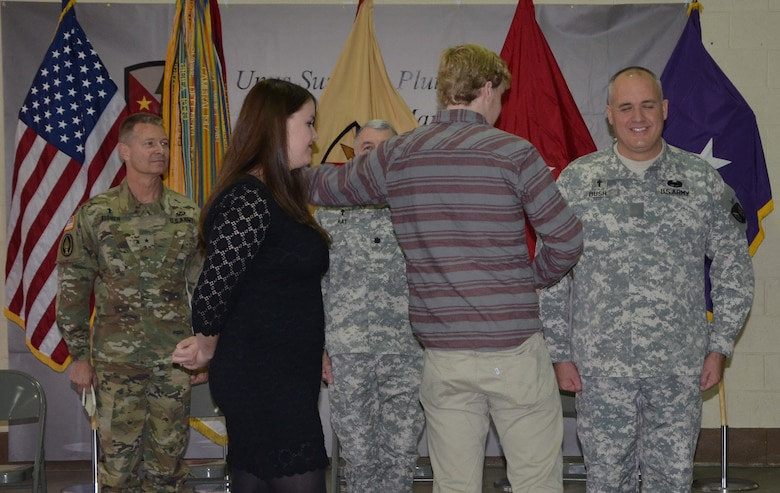 Chaplain (Maj.) Jeffery Bush's son, Andrew, removes the rank of major from Bush's uniform as his sister, Shelby, prepares to pin the rank of lieutenant colonel on her father's uniform. A promotion ceremony for Bush was held at the Army Reserve Sustainment Command in Birmingham. Also pictured are (back left to right): Chaplain (Brig. Gen.) Carlton Fisher, assistant chief of chaplains for mobilization and readiness in the Office of the Chief of Chaplains (OCCH) at the Pentagon, Chaplain (Lt. Col.) Brian Ray, command chaplain for the 377th Theater Sustainment Command of New Orleans, Louisiana.