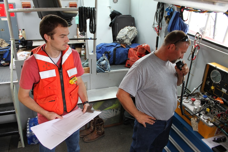 Dive team member, Mike Back (right), communicates with the underwater divers through a radio system in the dive boat while engineer, Josh Hendrix (left), takes detailed notes about what the divers are seeing and feeling during the inspection.