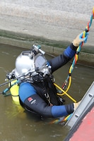 Dive team member John Snell enters the water at Locks and Dam 15 for an inspection of the shifting lower guidewall.