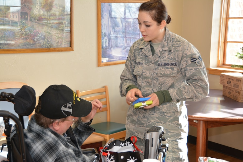 Senior Airman Talisa Edmundson of the 507th Civil Engineer Squadron, Tinker Air Force Base, Okla., assists a Veteran while opening a gift Dec. 22, 2015, at the annual Norman Veterans Center Angel Tree party in Norman, Okla. Through the Angel Tree program, 25 volunteers delivered gifts to 20 Veterans and nearly $700 collected from the 507th ARW, the 1st Aviation Standards flight, and the 513th Air Control Group.  (U.S. Air Force photo/Maj. Jon Quinlan)