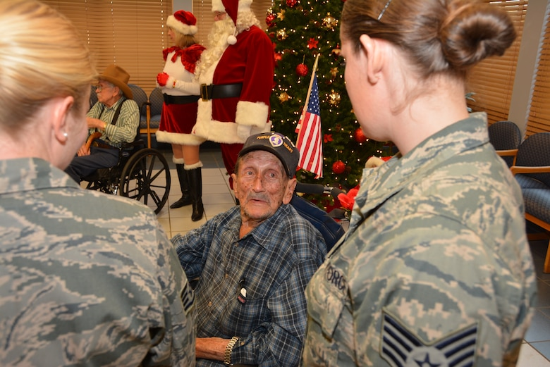 Veteran Robert Black, a Purple Heart recipient, tells Staff Sgts. Ashley White and Sarah Haggard of the 507th Air Refueling Wing a war story Dec. 22, 2015, at the Norman Veterans Center in Norman, Okla. Twenty-five members of the 507th ARW and their families attended the annual Angel Tree party, delivering gifts to 20 Veterans and nearly $700 toward the resident's benefit fund. (U.S. Air Force photo/Maj. Jon Quinlan)