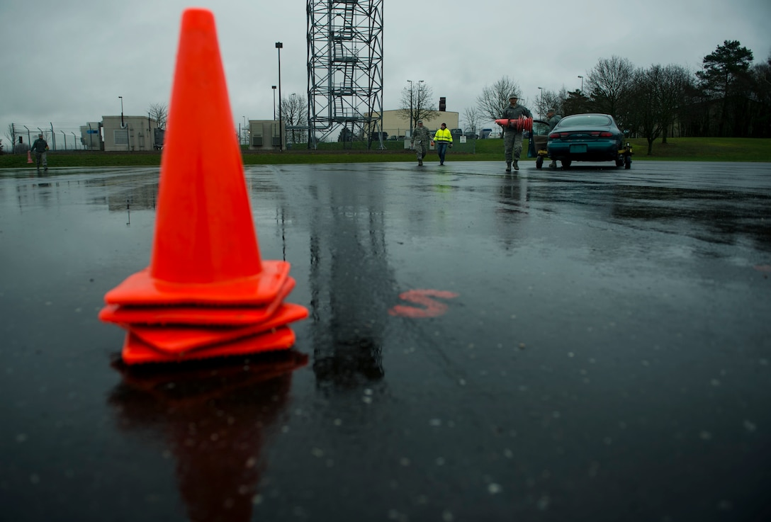 U.S. Air Force Staff Sgt. Brittany McGill, a 52nd Fighter Wing Safety occupational safety and health technician, picks up cones after a training session at the Saber Driving Course at Spangdahlem Air Base, Germany, Jan. 11, 2016. The safety team set up traffic cones around specific markers on the driving course designed for trainees to experience operating a vehicle during specific road conditions. (U.S. Air Force photo by Airman 1st Class Timothy Kim/Released)