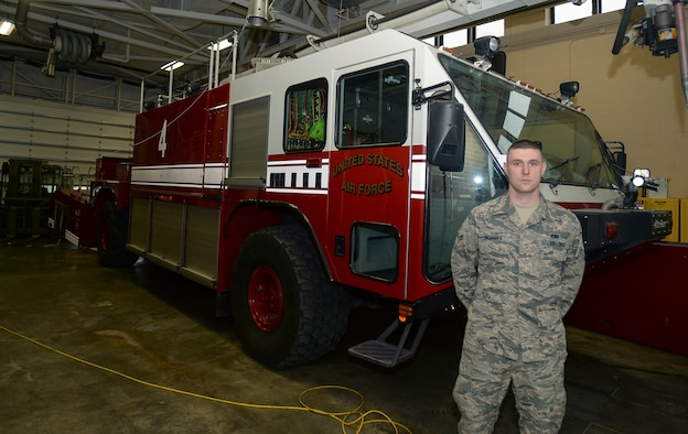 Airman 1st Class Jacob McQueen, 22nd Logistic Readiness Squadron firetruck vehicle maintenance, poses beside a P-19 firetruck Jan. 6, 2016, at McConnell Air Force Base, Kan. The firetruck is the similar to the one that had the starter replaced using salvaged parts from a snow-removal truck. (U.S. Air Force photo/Senior Airman Colby L. Hardin)