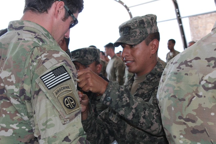 A Honduran soldier with the 2nd Honduran Airborne Brigade exchanges pins with a U.S. Service member with the Special Operations Command South (Forward) 7310 after a static-line training exercise involving both nations on Soto Cano Air Base, Honduras, January 11, 2016. Exercises such as these provide an opportunity to exchange knowledge and enhance partner nation interoperability. (U.S. Army photo by Maria Pinel)