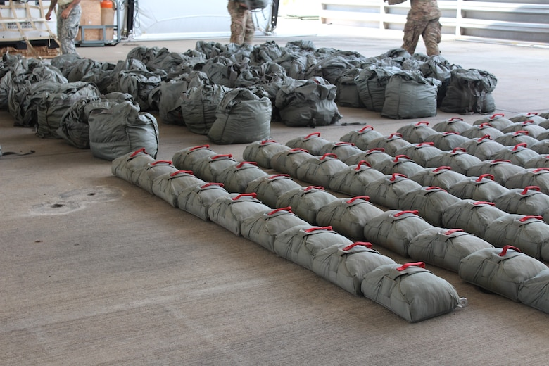 Service members with the Special Operations Command South (Forward) 7310 arrange parachutes after a static-line training exercise involving U.S. and Honduran soldiers on Soto Cano Air Base, January 11, 2016. Training events such as these enhance partner nation interoperability by providing an opportunity for the SOC FWD and the 2nd Honduran Airborne Brigade to exchange knowledge and experiences. (U.S. Army photo by Maria Pinel)