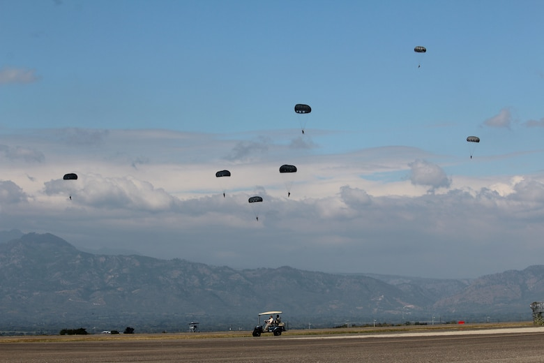 U.S. Army Soldiers with the Special Operations Command South (Forward) 7310 and Honduran soldiers with the 2nd Honduran Airborne Brigade descend over the flight line at Soto Cano Air Base during a static-line training exercise, January 11, 2016. Training events such as these enhance partner nation interoperability and provide an opportunity for SOC FWD and the Hondurans to exchange knowledge and experience. (U.S. Army photo by Maria Pinel)