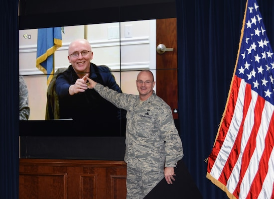 Defense Logistics Agency Aviation Commander Air Force Brig. Gen. Allan Day presents Gregory LaRue with a commander's coin during a video teleconference Jan. 6, 2016. LaRue is a material support technician for the Customer Operations Directorate of DLA Aviation at Ogden, Utah, and is DLA Aviation's November Employee of the Month.