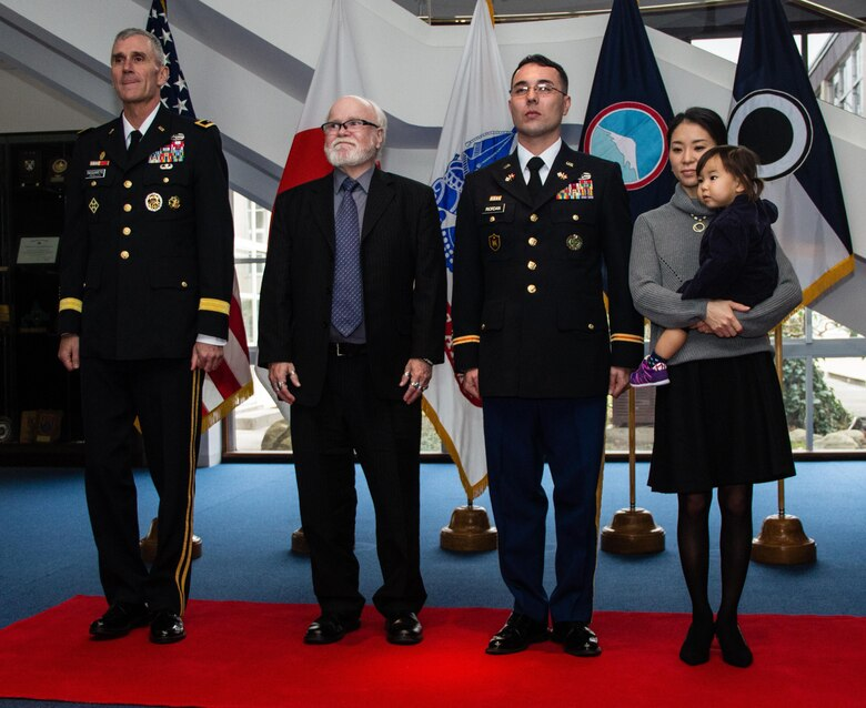 Army Maj. Gen. James F. Pasquarette (left), commanding general, U.S. Army Japan  (USARJ), stands at attention with Army 2nd Lt. Riki R. Riordan (third from left), signal officer, 311th Signal Command, during a direct commission ceremony conducted at USARJ's headquarters building in Camp Zama, Japan, Jan. 6, 2016. Riordan's father, Patrick (second from left), and his wife, Miyuki (right), pinned gold bars on their son and husband's shoulders, officially distinguishing him as a second lieutenant in the U.S. Army Reserve. Born and raised in Tokyo, Riordan is one of the first Soldiers in USARJ history to transition from the enlisted to officer ranks without having graduated from a military academy, Officer Candidate School, or Reserve Officer Training Corps program. (U.S. Army photo by Sgt. John L. Carkeet IV, U.S. Army Japan)