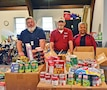 Left to right: Bob Beattie, industrial maintenance technician at the Douthit Gunnery Complex, Fred Siebe, manager of the Douthit Gunnery Complex, and Flora Lewis, executive director for the Open Door Community House in Junction City, stand with food donations from the Fort Riley staff's food drive from the beginning of October to Nov. 16.
