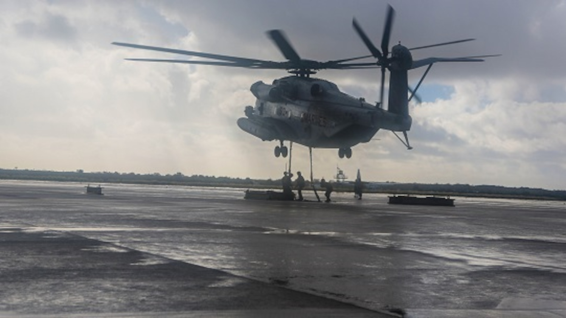 A CH-53E from Marine Heavy Helicopter Squadron (HMH) 465 hovers above as Marines with Combat Logistic Battalion (CLB) 11 rush in to attach 6,200-pound weight to the helicopter aboard Marine Corps Air Station Miramar, Calif., Jan. 7. Marines with CLB-11 support HMH-465 during daytime external lift training to prepare for future deployments. (U.S. Marine Corps photo by Lance Cpl. Harley Robinson/Released)
