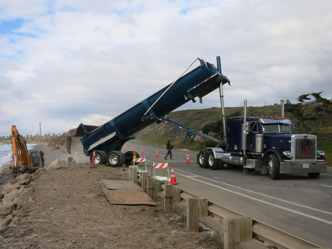 Heavy construction equipment delivers and places rock along a section of the Pacific Coast Highway in Carlsbad. The work is an emergency action authorized by the Corps to protect the coast and adjacent highway.