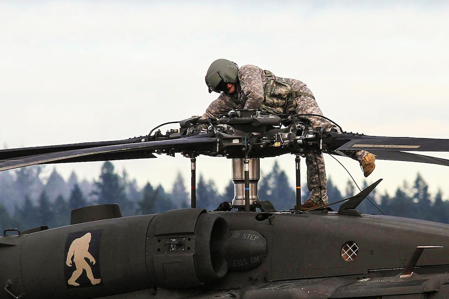 A soldier prepares a UH-60 Black Hawk on Joint Base Lewis-McChord, Wash., Jan. 9, 2016, to fly to the National Training Center on Fort Irwin, Calif. The soldier is assigned to the 7th Infantry Division's 2nd Battalion, 158th Aviation Regiment, 16th Combat Aviation Brigade. U.S. Army photo by Capt. Brian Harris