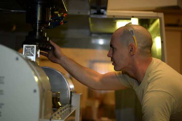 Staff Sgt. Adam Hebert, 28th Maintenance Squadron production supervisor, inspects a Haas VF 6 machine before cutting a metal block at Ellsworth Air Force Base, S.D., Jan. 6, 2016. The machine receives coding from a 3D model computer program and then uses that to cut out specific measurements and create a desired piece. The metals flight creates aircraft parts that cannot be ordered through a supplies list. (U.S. Air Force photo by Airman Sadie Colbert/Released)