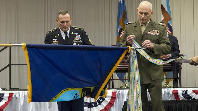 Command Sgt. Maj. William B. Zaiser holds the U.S. Southern Command flag while U.S. Marine Corps Gen. John F. Kelly attaches a Meritorious Unit Award streamer during the change of command ceremony at SOUTHCOM headquarters in Doral, Fla., Jan. 14, 2016. U.S. Navy Adm. Kurt W. Tidd is the new SOUTHCOM commander succeeding U.S. Marine Corps Gen. John F. Kelly.