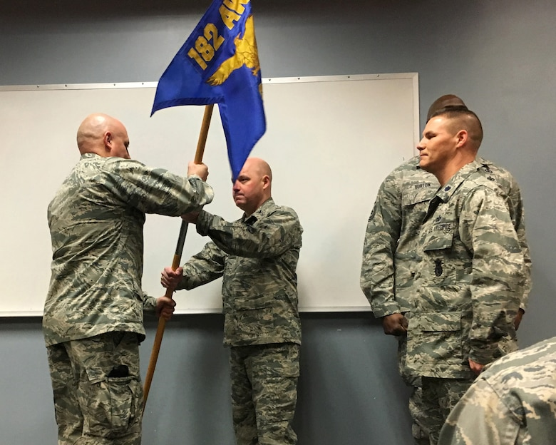 Maj. Gary Velasquez, left, accepts the 182nd Security Forces Squadron guidon from Col. Cory Reid, commander of the 182nd Mission Support Group, during a change of command Jan. 9, 2016. At right is Lt. Col. Todd Leach, outgoing Security Forces Squadron commander. (Air National Guard photo by Master Sgt. Blake Pumphrey)