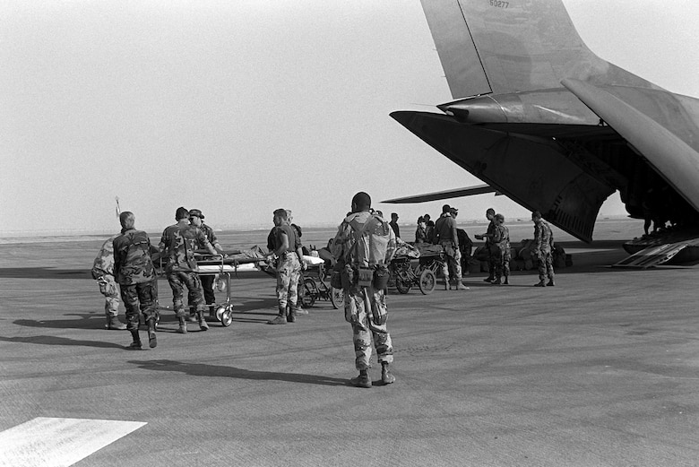 Medical personnel use litters to transport Cpl. Richard Ramirez, 1st Marine Division, and other wounded to a C-141B Starlifter aircraft. The patients are being medically evacuated from Al-Jubayl Air Base to Germany for treatment of wounds received during Operation Desert Storm.