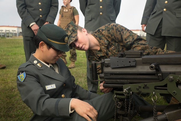 Cpl. Malynn Ochsner shows Japan Ground Self-Defense Force officer candidate Ayako Yukawa how to operate a MK19 machine gun, MOD 3 on Camp Kinser, Okinawa, Japan, Jan. 15. Three hundred and sixty JGSDF officer candidates visited Combat Logistics Regiment 35 to complete joint and combined operation requirements. The cadets watched Marine Corps Martial Art Program demonstrations, learned the capabilities of various machine guns the Marine Corps uses, and observed a static display of motor transportation vehicles. Ochsner, from Pflugerville, Texas, is a distribution management specialist with 3rd Supply Battalion, CLR-35, 3rd Marine Logistics Group, III Marine Expeditionary Force. (U.S. Marine Corps photo by Cpl. Robert Williams Jr./Released)