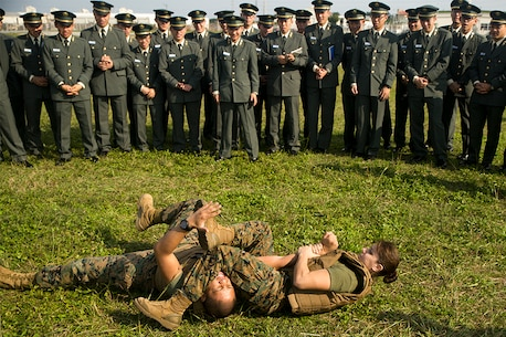 First Lt. Melissa Cooling demonstrates a Marine Corps Martial Arts Program arm bar to Japan Ground Self-Defense Force officer candidates on Camp Kinser, Okinawa, Japan, Jan. 15. Three hundred and sixty officer candidates visited Combat Logistics Regiment 35 to complete joint and combined operation requirements. The cadets watched Marine Corps Martial Art Program demonstrations, learned the capabilities of various machine guns the Marine Corps uses, and observed a static display of motor transportation vehicles. Cooling, from Southbury, Connecticut, is the current operations officer with CLR-35, 3rd Marine Logistics Group, III Marine Expeditionary Force. (U.S. Marine Corps photo by Cpl. Robert Williams Jr./Released)