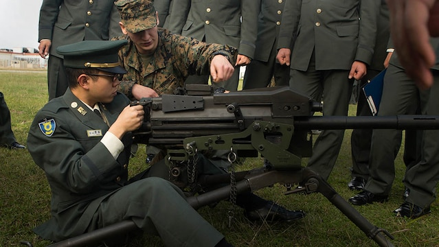 Pfc. Cooper Rottinghaus shows Japan Ground Self-Defense Force officer candidate Kazuhisa Takeda how to operate a MK19 machine gun, MOD 3 on Camp Kinser, Okinawa, Japan, Jan. 15. Three hundred and sixty JGSDF officer candidates visited Combat Logistics Regiment 35 to complete joint and combined operation requirements. Rottinghaus, from Stilwell, Kansas, is a maintenance management specialist with 3rd Supply Battalion, CLR-35, 3rd Marine Logistics Group, III Marine Expeditionary Force.