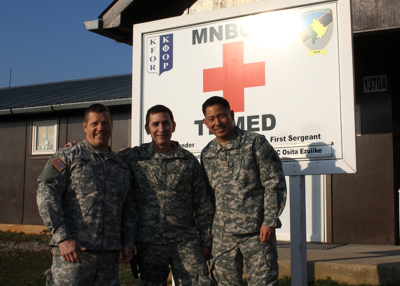U.S. Army Maj. David Whaley, Col. Edward Perez-Conde, and Maj. Kirk Shimamoto pose outside their Task Force Medical headquarters, Dec. 15, 2015, which serves as the installation hospital at Camp Bondsteel, Kosovo. The three U.S. Army Reserve officers responded to a civilian's life-threatening injuries during a four-day pass in Athens, Greece. Hailing from the 345th Combat Support Hospital in Florida, 308th Civil Affairs Brigade in Illinois, and 7234th Medical Support Unit in California, the three served as members of Multinational Battle Group-East and part of NATO's Kosovo Force mission in the Balkans. (U.S. Army photo by Lt. Col. Gilbert Buentello, Multinational Battle Group-East)