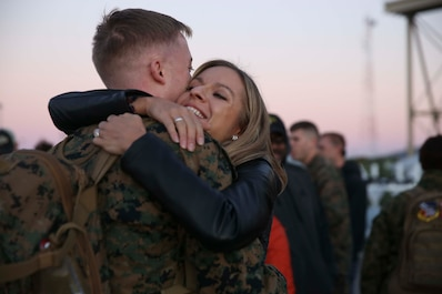 A Marine embraces his wife aboard Marine Corps Air Station Beaufort Jan. 12. The Marine is returning from a six-month deployment in the Western Pacific as part of the Unit Deployment Program. Marines deployed to Japan and Guam for six months to improve unit operability. The Marine is with Marine Fighter Attack Squadron 312, Marine Aircraft Group 31.