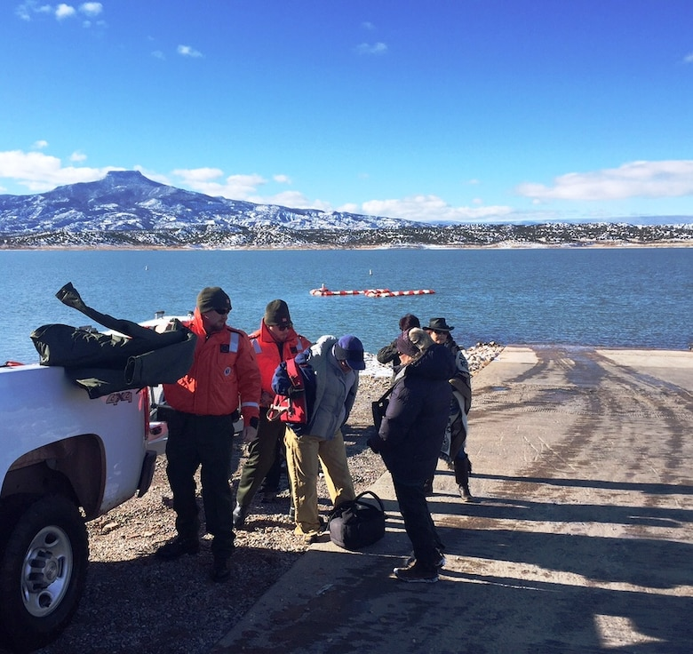 ABIQUIU LAKE, N.M. – Project Manager John Mueller and Lead Park Ranger Austin Kuhlman hand out life jackets to some of the volunteers before they get on a boat to count eagles, Jan. 9, 2016.