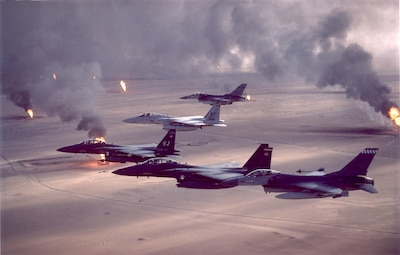 Pictures of an F-16A Fighting Falcon, F-15C Eagle and F-15E Strike Eagle fighter aircraft fly over burning oil field sites in Kuwait during Operation Desert Storm.