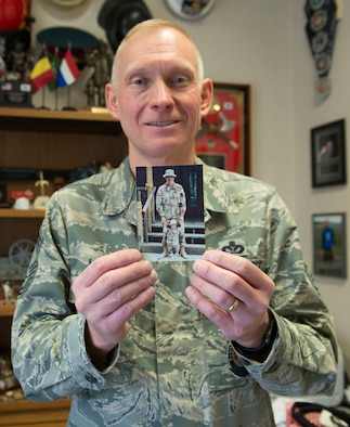 """Chief Master Sgt. Richard Lien, 366th Civil Engineer Squadron fire department chief, holds a Desert Storm-era photo of himself with his oldest son, Jan. 13, 2016, at Mountain Home Air Force Base, Idaho. """"I didn't come home for a parade,"""" Lien said. """"This is my victory parade, being with my oldest son."""" (U.S. Air Force Photo by Airman Chester Mientkiewicz/RELEASED)"""