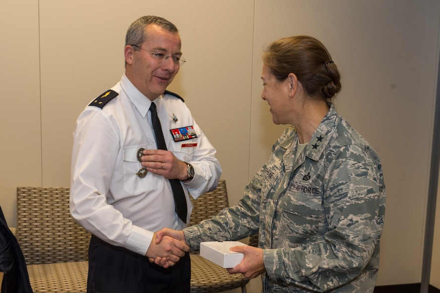 U.S. Air Force Maj. Gen. Shelia Zuehlke (left), mobilization assistant to the commander, 24th Air Force and Air Forces Cyber Command (AFCYBER), shakes hands with French Air Force Brig. Gen. Thierry Combel, Deputy Director General of Employment and Training-Air Force Human Resources, after the two exchanged small gifts during his visit to Headquarters, 24AF - AFCYBER, Joint Base San Antonio - Lackland, Texas, Jan 13. Combel, along with other members of a cybersecurity delegation visited to discuss how the U.S. and French Air Force's approach cyber organization, training, and exercise participation as well as to facilitate future partnerships and engagements.. (U.S. Air Force photo by Master Sgt. Luke P. Thelen/Released)