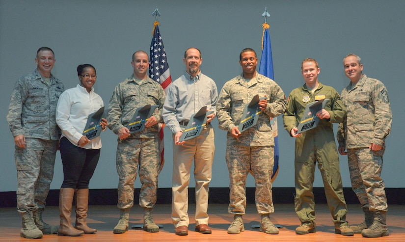 Colonel John Lamontagne, 437th Airlift Wing commander (far left), and Chief Master Sgt. Kristopher Berg, 437th AW command chief (far right), stand with the awardees from the 437th AW quarterly awards ceremony at the Air Base Theater on Joint Base Charleston – Air Base, S.C., on Jan. 14, 2016. From left to right the recipients are Tiffany Gamble, 437th Maintenance Squadron unit program coordinator, for the civilian category I award, MSgt. Trapper Otto, 437th MXS hydraulic section chief, for the senior non-commissioned officer award, Gary Wettengel, 437th Operations Support Squadron, combat tactics aircraft weapons specialist, for the category civilian II award, Capt. Ryan Nichols, 437th OSS airfield operations flight commander, for the company grade officer award and TSgt. David Flory, 16th Airlift Squadron operations support flight chief, for the non-commissioned officer award. Senior Airman Gloria Davis-Phillips, 437th Maintenance Group aircraft maintenance unit analyst, won the  Airman of the quarter award but was not present to receive it personally. (U.S. Air Force photo/Airman 1st Class Thomas T. Charlton)