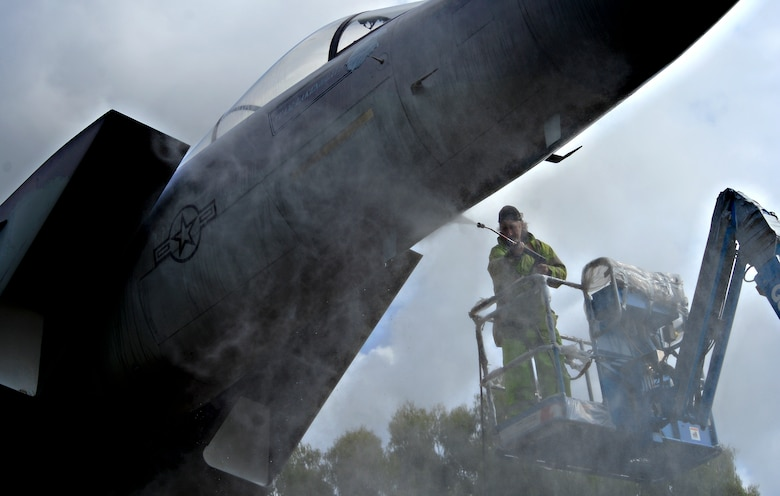 Workers from Fangeos Painting and Decorating Contractors in Essex pressure wash the static displays before repainting them at Royal Air Force Lakenheath, England, July 22, 2015. Working with the local community is vital in accomplishing the mission of the 48th Fighter Wing. (U.S. Air Force photo by Senior Airman Erin Trower/Released)