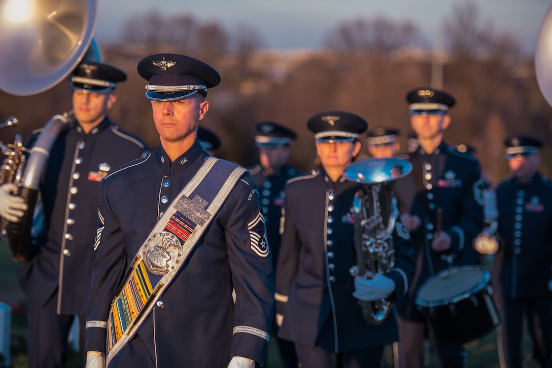 Drum Major, Senior Master Sgt Daniel Valadie, leads the Ceremonial Brass during a funeral for a fallen hero at Arlington National Cemetery. (U.S. Air Force Photo/ released)